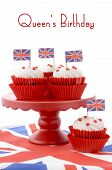 stock photo of red velvet cake  - Red white and blue theme cupcakes on red cake stand with UK Union Jack flags on white wood table with Queens Birthday sample text - JPG