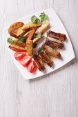 stock photo of ribs  - Pork ribs potatoes and tomatoes on a plate on the table - JPG