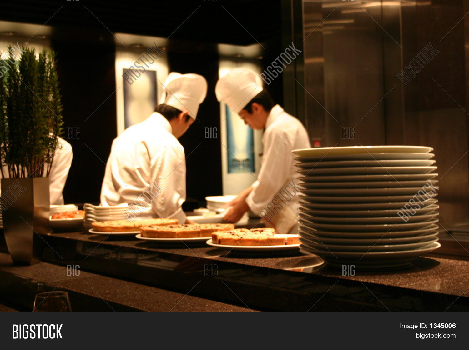 Busy Restaurant Kitchen Two Chefs Working In A Busy Restaurant Kitchen Stock Photo & Stock