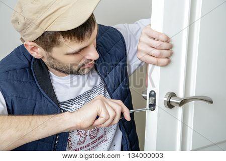 Man carpenter fixing lock in door with screwdriver at home. White door. Close-up.
