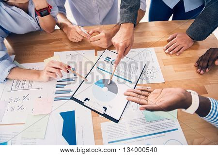 Important project. Pleasant professional involved colleagues sitting at the table and pointing the graph while having a discussion