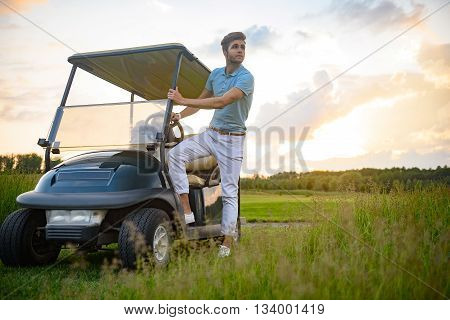 Day well spent. Handsome man standing with his golf cart and planning to drive with sun setting in background