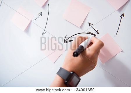 Involved in work. Pleasant person holding highlighter and writing on the board while working in the office