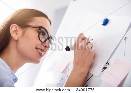 Write it down. Positive delighted smiling woman holding pen and making notes on the board while expressing gladness