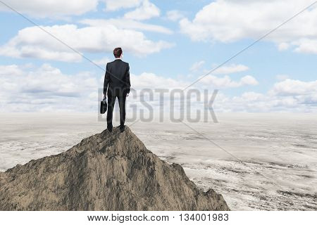 Research concept with businessman standing on mountain top and looking at desert