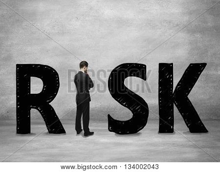 Business risk concept with thoughtful businessman standing instead letter I on concerete background