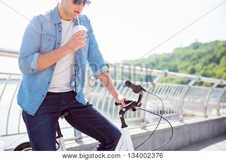 I am thirsty. Thoughtful guy drinking a tasty beverage and looking down while sitting on the bike and having a rest