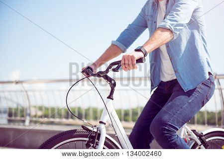 Join me. Picture of a man riding a bike and holding a handbrake with his hand with a river on the background