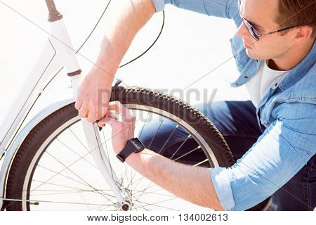 It is not a big deal. Concentrated good looking young man trying to repair his bike on the white background