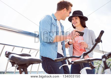 Listen to me. Cheerful young man laughing with a pretty young woman in hat while holding a smartphone and standing near bikes