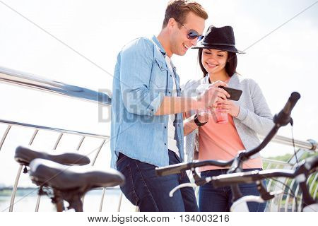 Have a look. Joyful smiling man and pleasant beautiful woman looking at the phone while standing near bicycles and having a drink