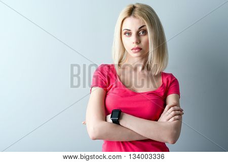 Portrait of cheerful blond girl looking at camera with seriousness. She is standing and posing with crossed arms. Isolated and copy space in left side