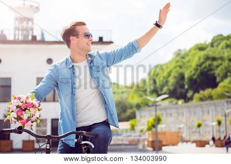 I am here. Cheerful young man with sunglasses sitting on a bike and waving a hand in sign of salutation while holding flowers