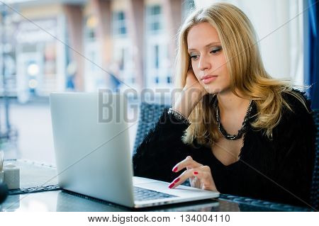 Young gorgeous woman drinking coffee while sitting with open laptop computer outdoors, female freelancer working on notebook in sidewalk cafe, pretty student girl surfing the net outside on terrace.