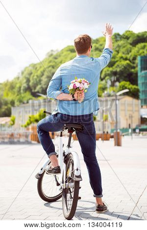 Making a surprise. Handsome young man holding flowers behind his back and waving a hand in sign of salutation while sitting on a bike