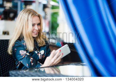 young woman making self portrait using smartphone. girl making selfie. woman in cafe. woman alone. self portrait in cafe outdoors. smile. smilimg. gadget. self portrait. coffe break. coffee time.