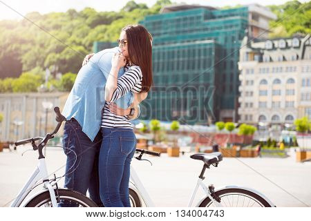 Missed you. Handsome tall man embracing a pleasant young woman with sunglasses while standing with bikes