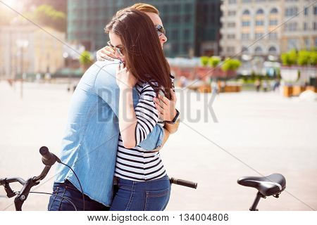 Romantic vibes. Handsome delighted man embracing a beautiful young woman with sunglasses while standing with bikes