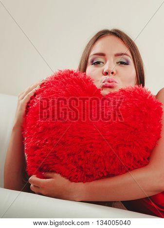 Smiling pretty cute young woman girl hugging red heart shape pillow sitting on white sofa couch. Valentines day love.