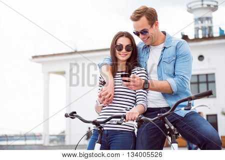 Just look. Handsome smiling guy and pleasant woman looking at the smartphone while sitting on the bicycles