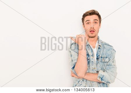 Handsome man with open mouth showing way with finger