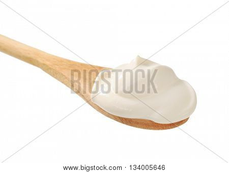 Sour cream on a wooden spoon isolated on white