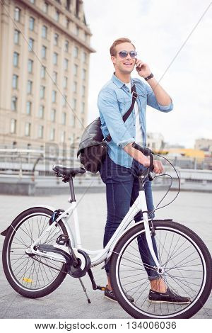 Yes I am here. Contended smiling young man talking on the phone while standing near a bicycle