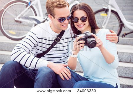 Nice shot. Happy young woman in sunglasses showing photos on the camera to a contented young man while sitting on the stairs