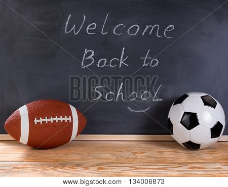 Football and soccer ball on desktop. Erased black chalkboard in background along with welcome back to school message to students.
