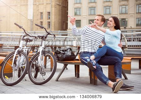 How it is amazing. Relaxed smiling man and charming young woman sitting at the table and having a rest after riding on bikes