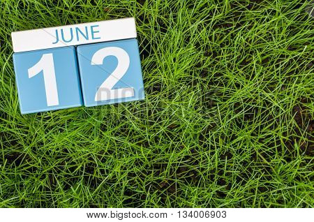 June 12th. Image of june 12 wooden color calendar on greengrass lawn background. Summer day, empty space for text.