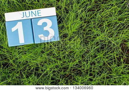 June 13th. Image of june 13 wooden color calendar on greengrass lawn background. Summer day, empty space for text.