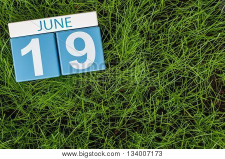 June 19th. Image of june 19 wooden color calendar on greengrass lawn background. Summer day, empty space for text.