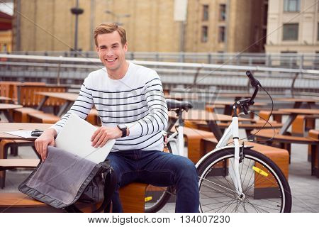 Always connected. Cheerful smiling young man taking out of a bag his laptop while sitting at the cafe near a bike and looking at the camera