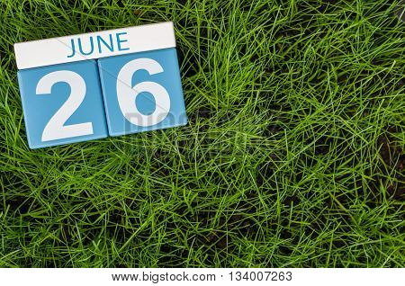 June 26th. Image of june 26 wooden color calendar on greengrass lawn background. Summer day, empty space for text.