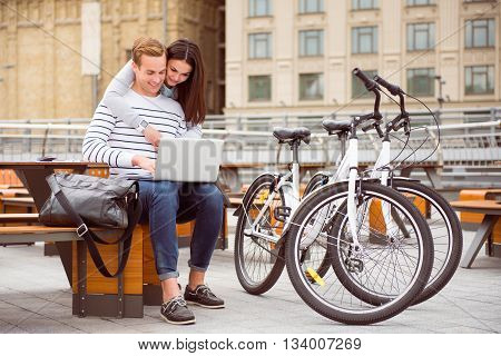 Feel good. Beautiful young woman hugging a handsome man who tapping on the laptop while sitting at the table