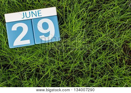 June 29th. Image of june 29 wooden color calendar on greengrass lawn background. Summer day, empty space for text.