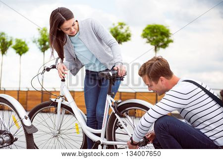 It is not a big deal. Young pensive man fixing a bicycle for a charming woman
