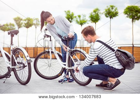 Be careful. Handsome pensive man fixing a wheel of a bicycle for a charming woman in the city