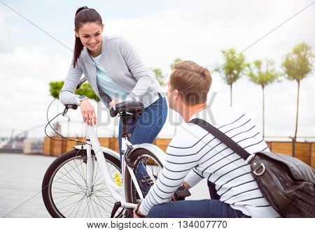Let me do it. Beautiful woman has a malfunction with her bike and handsome man is going to fix it