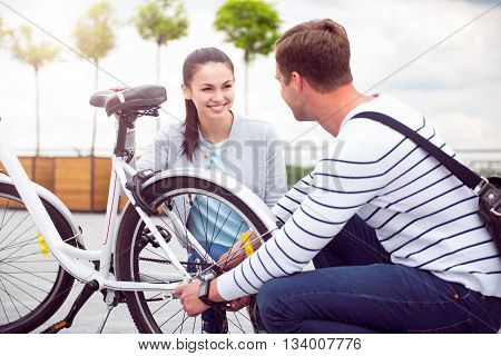 Visual contact. Pretty woman and handsome man squatting near the bike and looking at each other