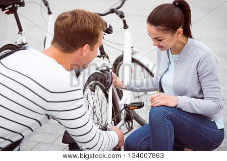 Embarrassed girl looking at the bike and man staring at her with a great interest