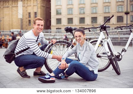 Feeling pleased. Smiling young couple sitting near the bikes with happy faces and posing for the photo