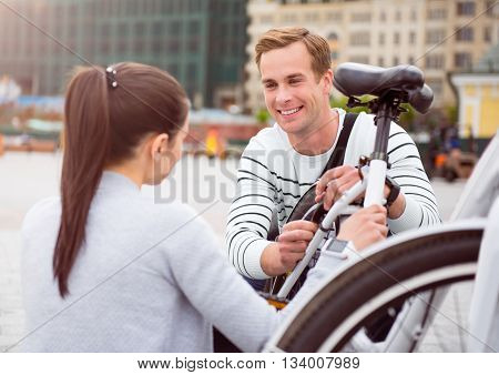 Good day with you. A young handsome guy looking with love at a beautiful woman while fixing a bike