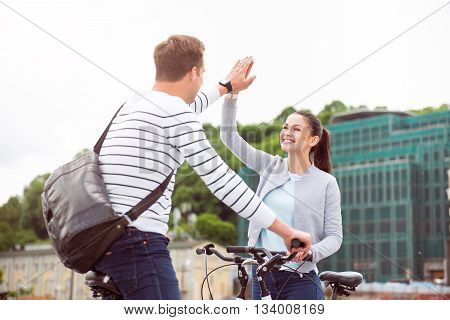 Hey you. Sincere young man making a gesture of high five with a pretty woman while riding with her