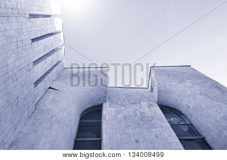 Architecture modern background - perspective bottom view of high building architecture details of concrete and glass. Cold urban tones tones applied. Architecture futuristic cityscape.