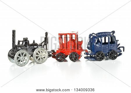 Old used metal toy train with locomotive and wagons over white background