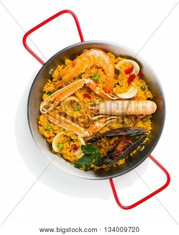 Top view of paella with langoustine mussel prawn and vegetables in a small paellera isolated on a white background.