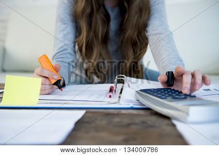 close up hands with pen of woman suffering stress doing domestic accounting paperwork bills and invoices worried and stressed at home sofa couch with bank folders calculator and receipts