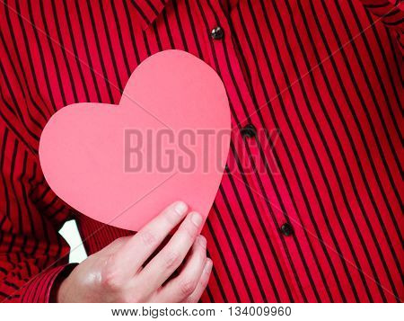 Romance feelings symbolism affection concept. Person holding heart cutout. Adult man in red shirt showing love symbol.